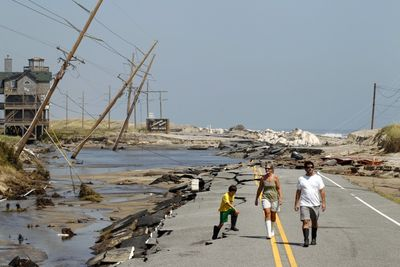 151971-residents-walk-along-hwy-12-after-it-was-destroyed-by-hurricane-irene-