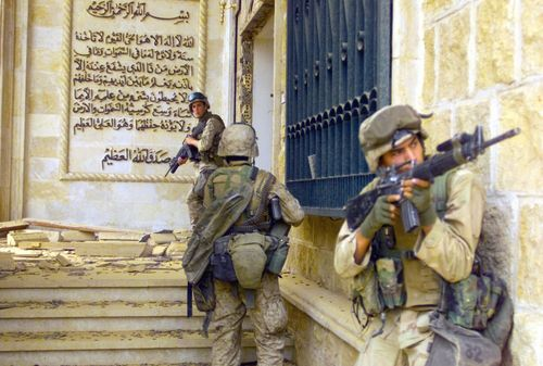 Marines-cover-each-other-with-m16a2-assault-rifles-as-they-prepare-to-enter-one-of-saddam-husseins-palaces-in-baghdad-during-operation-iraqi-freedom-in-2003