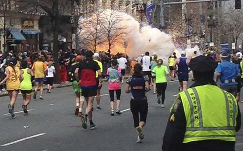 Runners-continue-to-run-toward-the-finish-line-of-the-boston-marathon-as-explosions-erupt-the-bombing-led-to-one-of-the-most-high-profile-manhunts-in-recent-m
