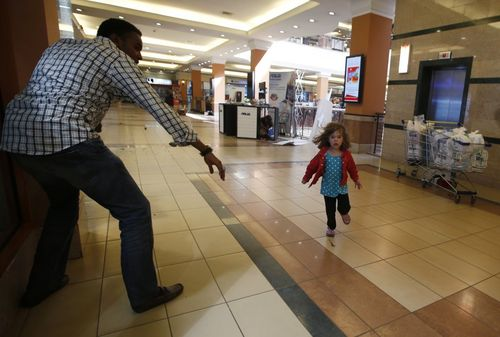 A-child-runs-to-safety-as-armed-police-hunt-gunmen-who-went-on-a-shooting-spree-at-the-westgate-shopping-mall-in-nairobi-kenya-the-attack-resulted-in-72-death