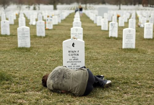 Lesleigh-coyer-lays-down-in-front-of-the-grave-of-her-brother-soldier-ryan-coyer-who-died-from-injuries-sustained-in-afghanistan